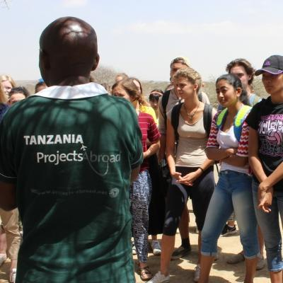 A group of Community volunteers are outside being taught about Maasai Culture during their Community volunteer work in Tanzania.